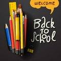 Back to school title words with realistic school items with colored pencils, pen and ruler in a black texture background