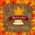 Back to school wooden background with frame of leaves with maple leaf, books and ribbon with text