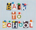 Back to school the words in cut out magazine letters pinned a background of blue lined graph paper Stock Images