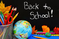Back to school written on a blackboard with supplies Royalty Free Stock Image
