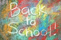 Back to school written in chalk the words are white sidewalk on a background of rainbow tye dye colors drawn on the pavement Royalty Free Stock Photos