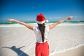Back view of beautiful girl in santa hat walking like a bird on white beach this image has attached release Royalty Free Stock Photography