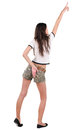 Back view of beautiful young woman in shorts pointing at wall Stock Image