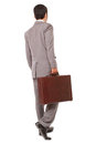 Back view of a business man standing and holding a briefcase isolated on white background Stock Photo