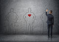 Back view of a businessman drawing men's silhouettes on concrete wall. The middle one with red heart in its chest. Royalty Free Stock Photo