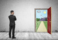 Back view of businessman looking at open door with hand drawn sunny mountain landscape and road Royalty Free Stock Photo