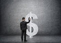 Back view of businessman touching big concrete dollar sign Royalty Free Stock Photo
