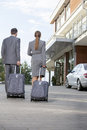 Back view of businesspeople walking with luggage outside hotel Stock Photography