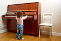 Back view. A child stands in front of the piano and plays a melody. Little pianist learning to play the piano. Baby, child