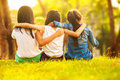 Back view of cute girls seated on green grass and relaxing Royalty Free Stock Photos