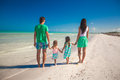 Back view of family of four walking along the beach on caribbean beach vacation Royalty Free Stock Images
