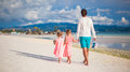 Back view of father and his two little daughters walking by the sea this image has attached release Royalty Free Stock Image