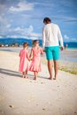 Back view of father and his two little daughters walking by the sea this image has attached release Royalty Free Stock Photography