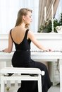 Back view of female pianist sitting and playing piano woman in black dress concept music enjoyment Stock Photography