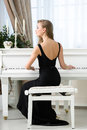 Back view of female sitting and playing piano woman in black dress concept music entertainment Stock Photos
