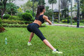 Back view of fit girl doing side lunge exercises outdoors