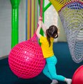 Back view. funny girl with ponytails hangs on a rope and crawls on a big red ball