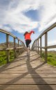 Back view of girl running in a wood boardwalk Royalty Free Stock Photo
