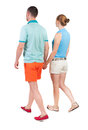 Back view going couple in shorts walking friendly girl and guy holding hands rear people collection backside of person Royalty Free Stock Photo