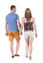 Back view going couple in shorts walking friendly girl and guy holding hands rear people collection backside of person Royalty Free Stock Photos