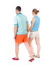 Back view going couple in shorts walking friendly girl and guy holding hands rear people collection backside of person Royalty Free Stock Image