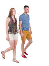 Back view going couple in shorts walking friendly girl and guy holding hands rear people collection backside of person Stock Image