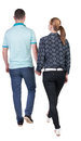 Back view going couple walking friendly girl and guy holding hands rear people collection backside of person isolated Royalty Free Stock Photography