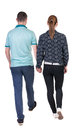 Back view going couple walking friendly girl and guy holding hands rear people collection backside of person isolated Royalty Free Stock Image