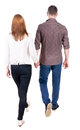 Back view going couple walking friendly girl and guy holding hands rear people collection backside of person isolated Stock Photo