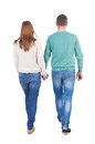 Back view going couple walking friendly girl and guy holding hands rear people collection backside of person isolated Royalty Free Stock Photo