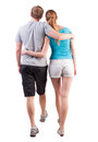 Back view of going young couple man and woman walking beautiful girl and handsome guy in shorts together rear view people Royalty Free Stock Photo