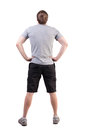 Back view of handsome man in t shirt and shorts looking up standing young tourist looks at showplace rear view people collection Stock Images