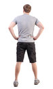 Back view of handsome man in t shirt and shorts looking up standing young tourist rear view people collection backside view of Royalty Free Stock Images