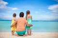 Back view of happy father with his two daughters on tropical beach vacation this image has attached release Stock Photo
