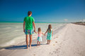 Back view of happy father with his two kids walking on tropical beach vacation this image has attached release Stock Photography