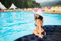 Back view happy female with perfect figure in a black bikini and hat sit on a mattress in the swimming pool on resort Royalty Free Stock Photo