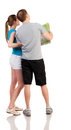 Back view journey of the young happy couple on vacation looking at the map travelers men and a women in shorts consider recreation Royalty Free Stock Image
