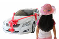Back view of little girl looking at new car with red bow as pres Royalty Free Stock Photo