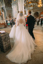 The back view of the long wedding dress of the bride and groom during the ceremony in the church.