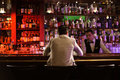 Back view of a man ordering drink to a bartender Royalty Free Stock Photo