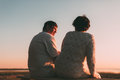 Back view a married couple a silhouette sitting on a bench. Royalty Free Stock Photo