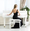 Back view of musician sitting and playing piano woman in black dress concept music arts Stock Images