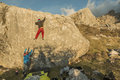 Back view of people climbing rock boulder in sunset Royalty Free Stock Photo