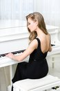 Back view of pianist sitting and playing piano woman in black dress concept music creative hobby Royalty Free Stock Images
