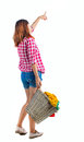 Back view of pointing woman with  basket  dirty laundry. girl is engaged in washing. Royalty Free Stock Photo
