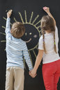 Back view of siblings drawing sun on blackboard while holding hands Royalty Free Stock Photo