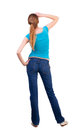 Back view of standing young beautiful blonde woman in blue t shirt and jeans girl watching into the distance rear view people Stock Images