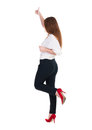 Back view of standing young redhead business woman showing thumb up beautiful businesswoman in black suit gesturing ok sign rear Royalty Free Stock Image