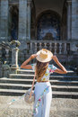 Back view of a stylish female tourist admires of a beautiful architectural building during walking in foreign city, young woman tr Royalty Free Stock Photo