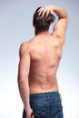 Back view of a topless young man standing with hand in his pocket and the other in his hair while looking up on gray Stock Images